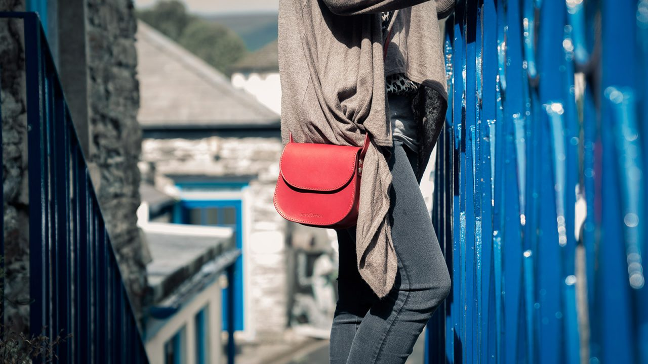 Femme avec petit sac épaule en cuir rouge.