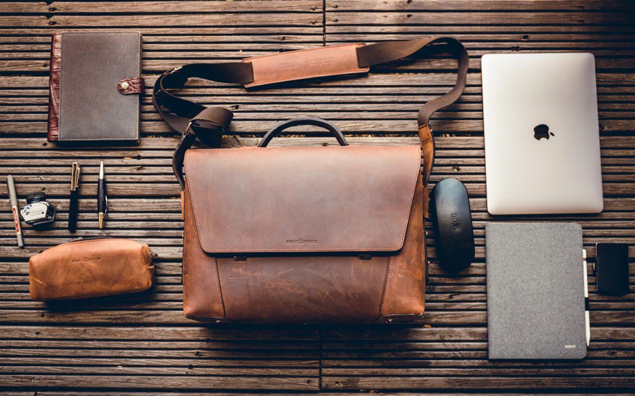 Serviette en cuir marron avec accessoires de travail.