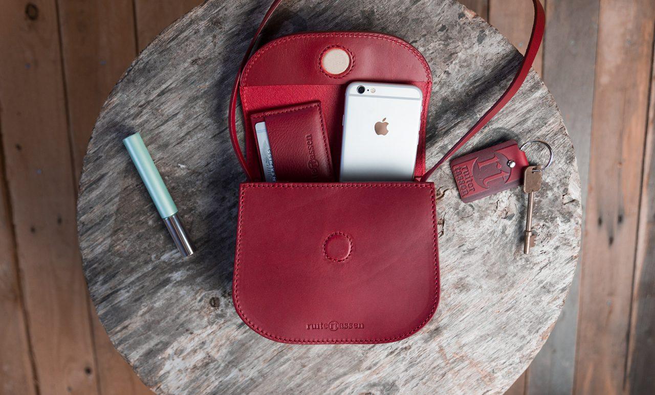 Petit sac rouge en cuir ouvert avec accessoires.
