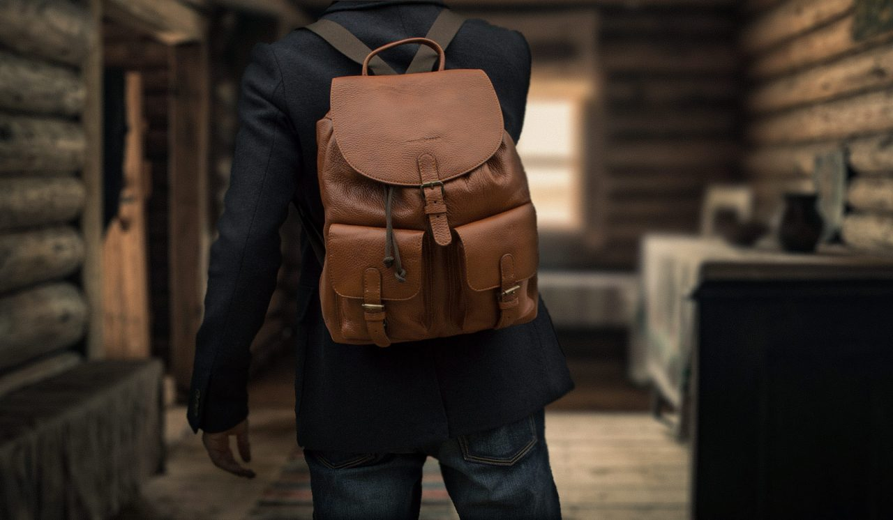 Homme avec sac à dos souple cognac.