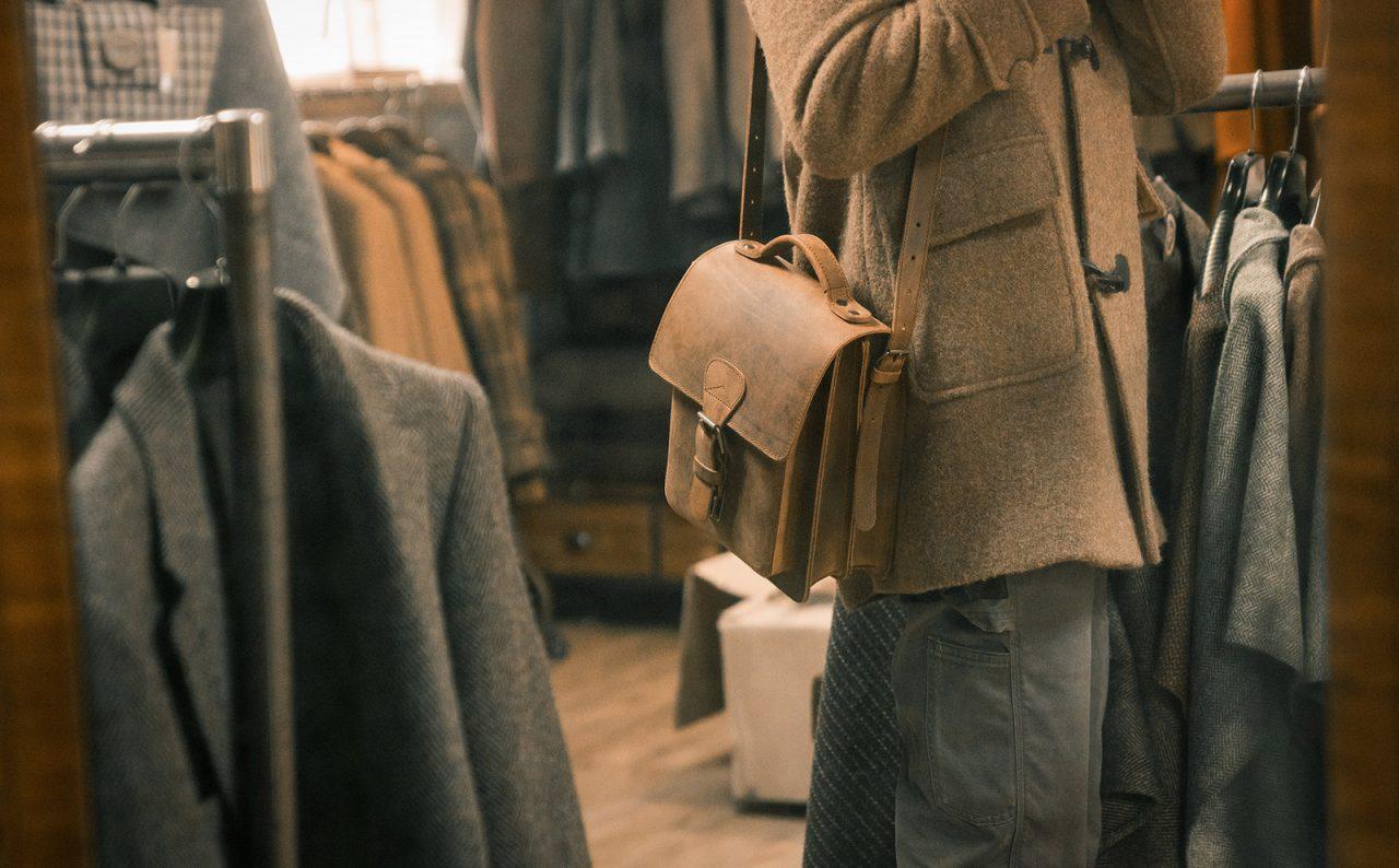 Homme avec sacoche cuir marron portée par un homme en bandoulière.