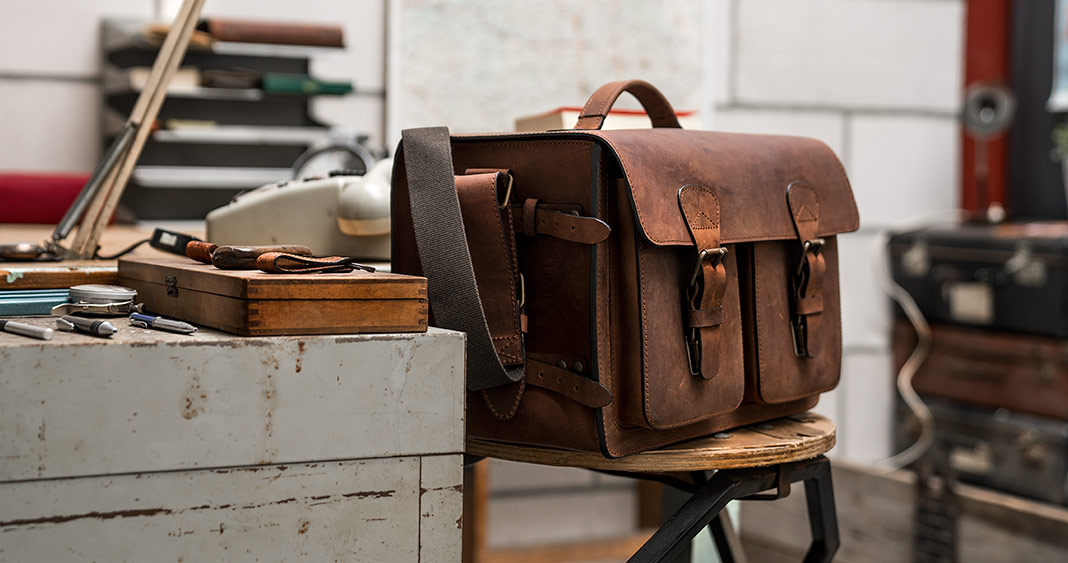 Grand sac photo en cuir marron dans un atelier.