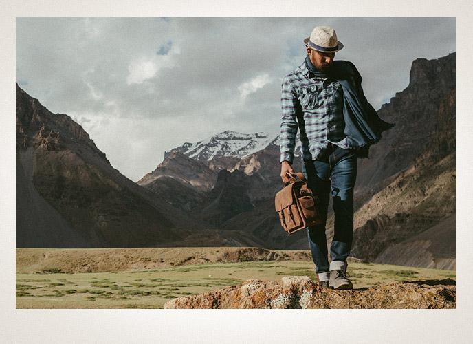 Homme avec sac photo bans beau paysage.