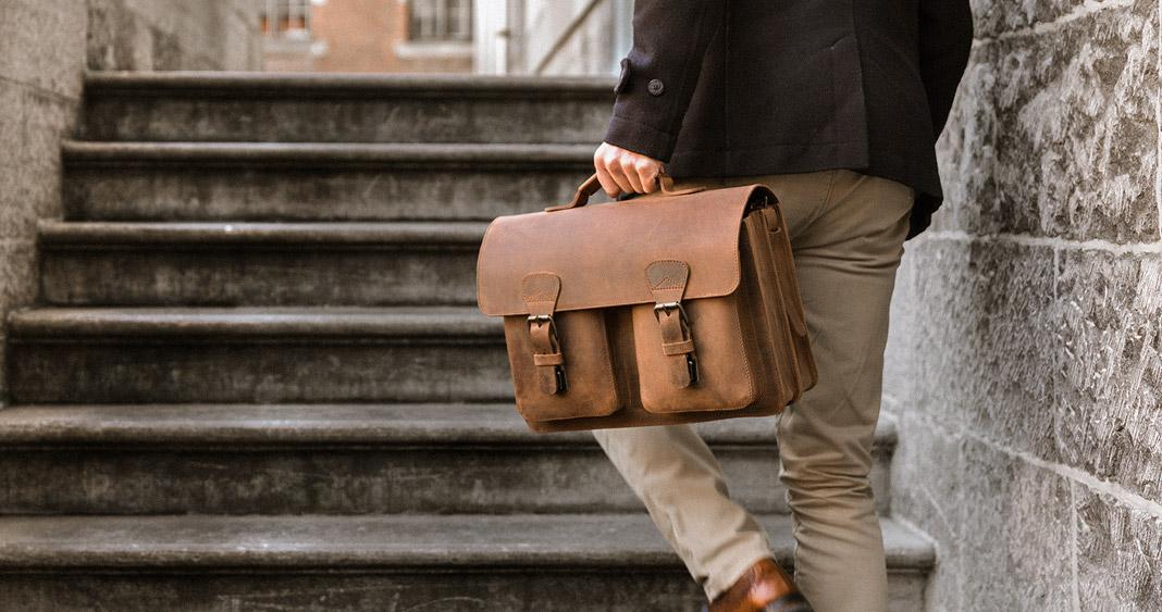 Enseignant avec grand cartable cuir marron.