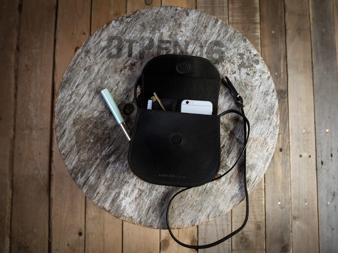 Petit sac noir ouvert avec accessoires.