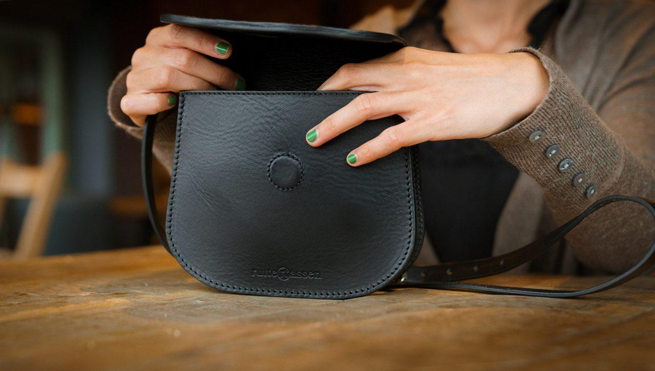 Femme ouvre sac pochette en cuir noir.
