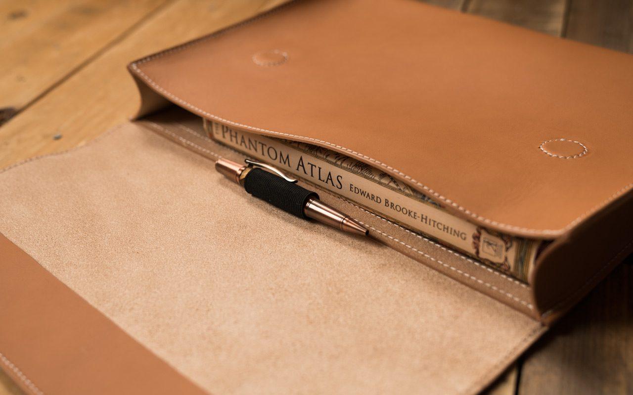Livre et stylo dans une pochette en cuir beige.