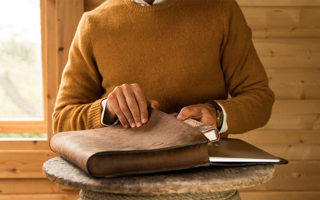 Homme ouvre une pochette en cuir marron.