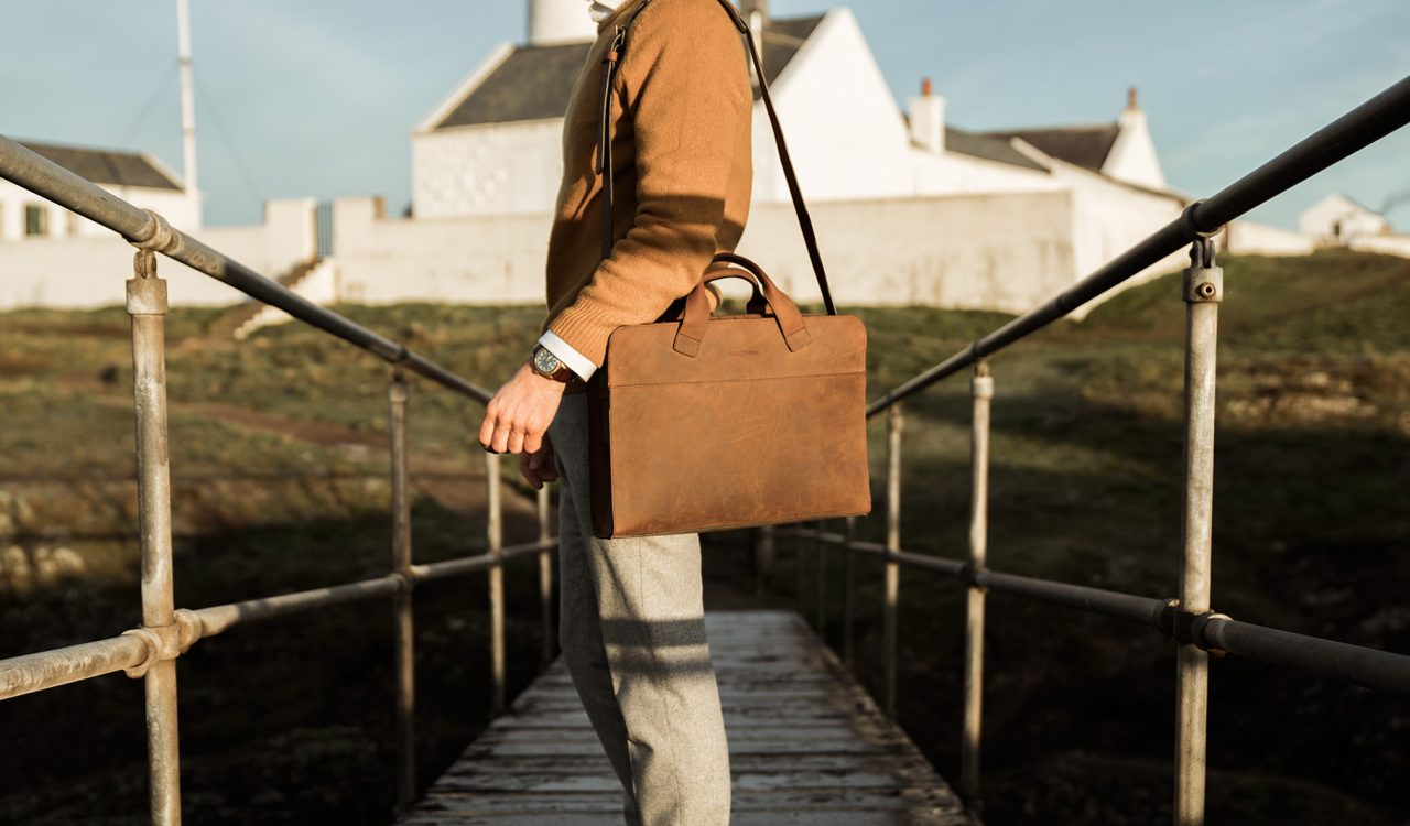 Sacoche professionnelle cuir pour homme portée à l'épaule.