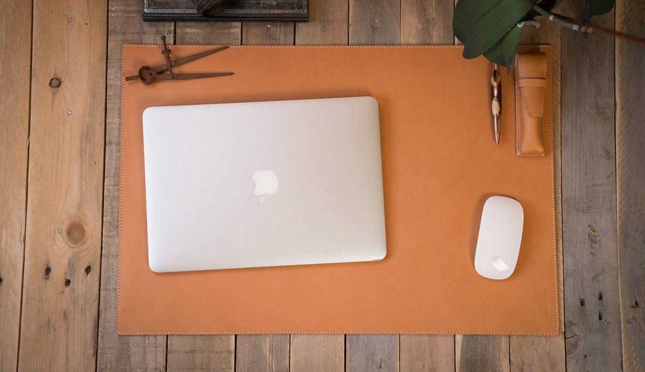 Sous-main cuir beige avec ordinateur.