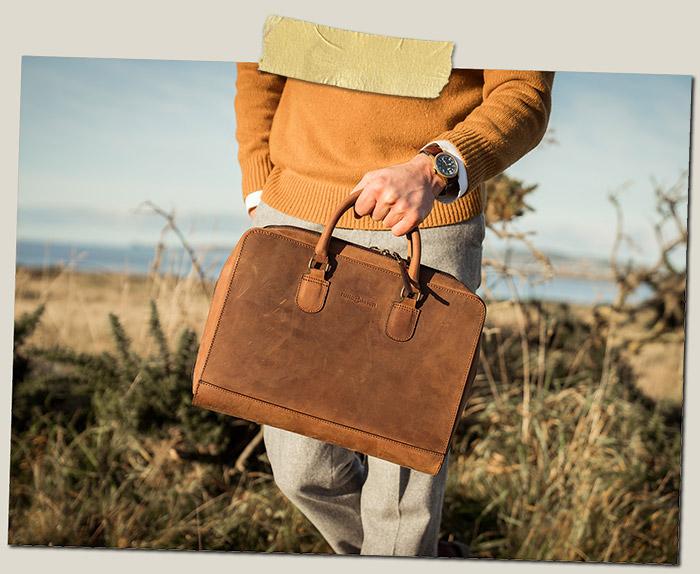 Sac portfolio en cuir marron tenu par un homme.
