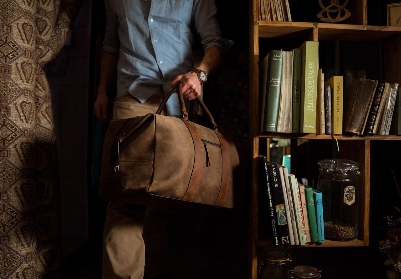 Homme qui porte un grand sac de voyage en cuir duffle.