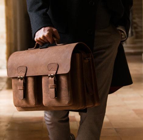 Cartable vintage en cuir marron porté par un homme.
