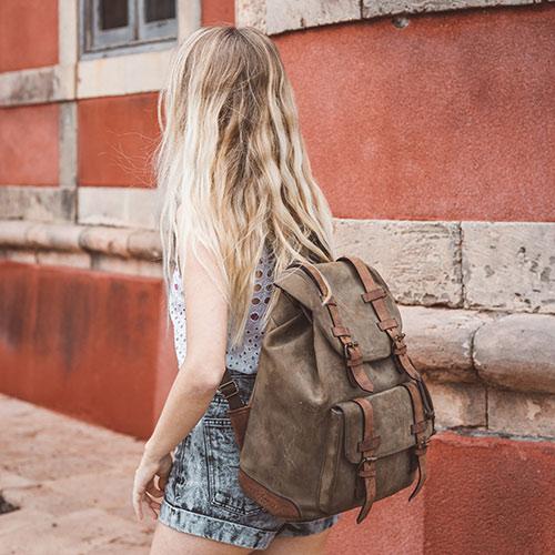 Grand sac à dos cuir porté par une femme.