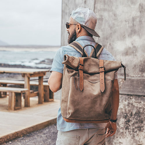Grand sac à dos cuir porté par un homme.