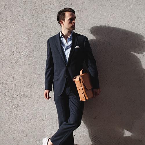 Serviette cuir marron clair portée sous le bras par un homme.
