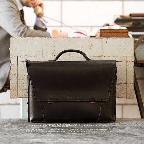 Serviette pour homme en cuir noir dans un bureau.