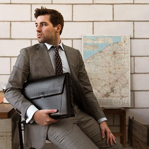 Homme avec pochette cuir noir sous le bras.