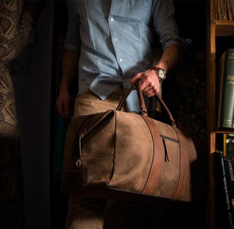 Beau sac weekend en cuir porté par un homme.