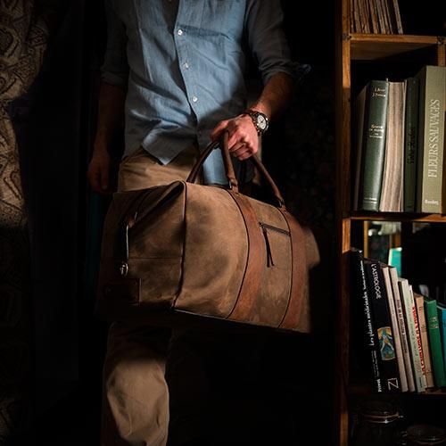 Homme avec grand sac de voyage en cuir.