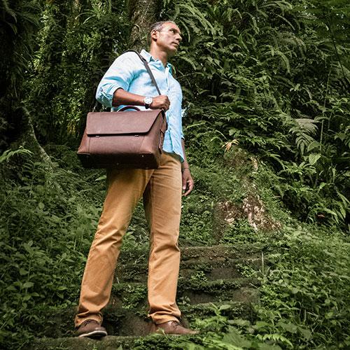 Homme avec serviette en cuir marron dans la forêt.