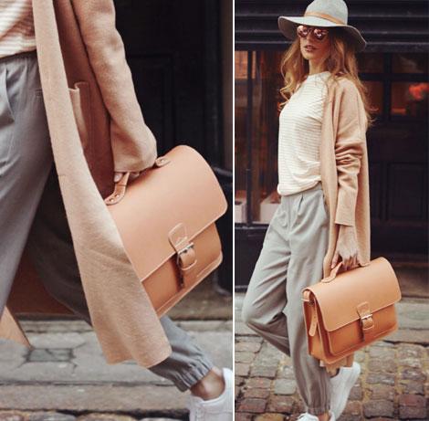 Femme élégante avec porte-documents en cuir marron clair.