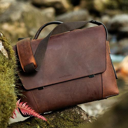 Belle serviette de travail en cuir marron dans la forêt.